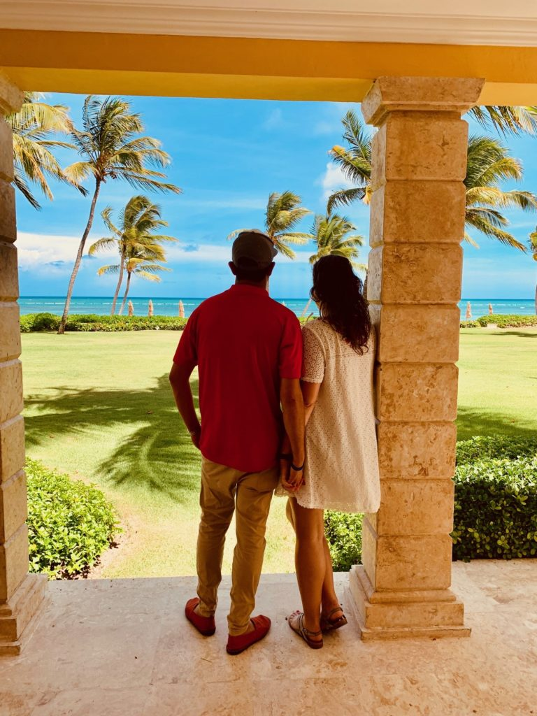 A couple looks out to the sea from a patio at Tortuga Bay